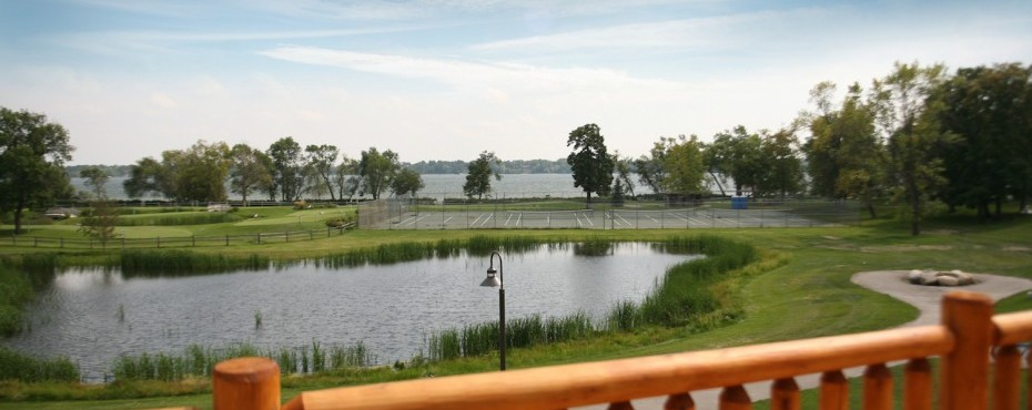 View of the lake from a deck with a tennis court in the background