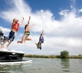 Family jumping into a lake